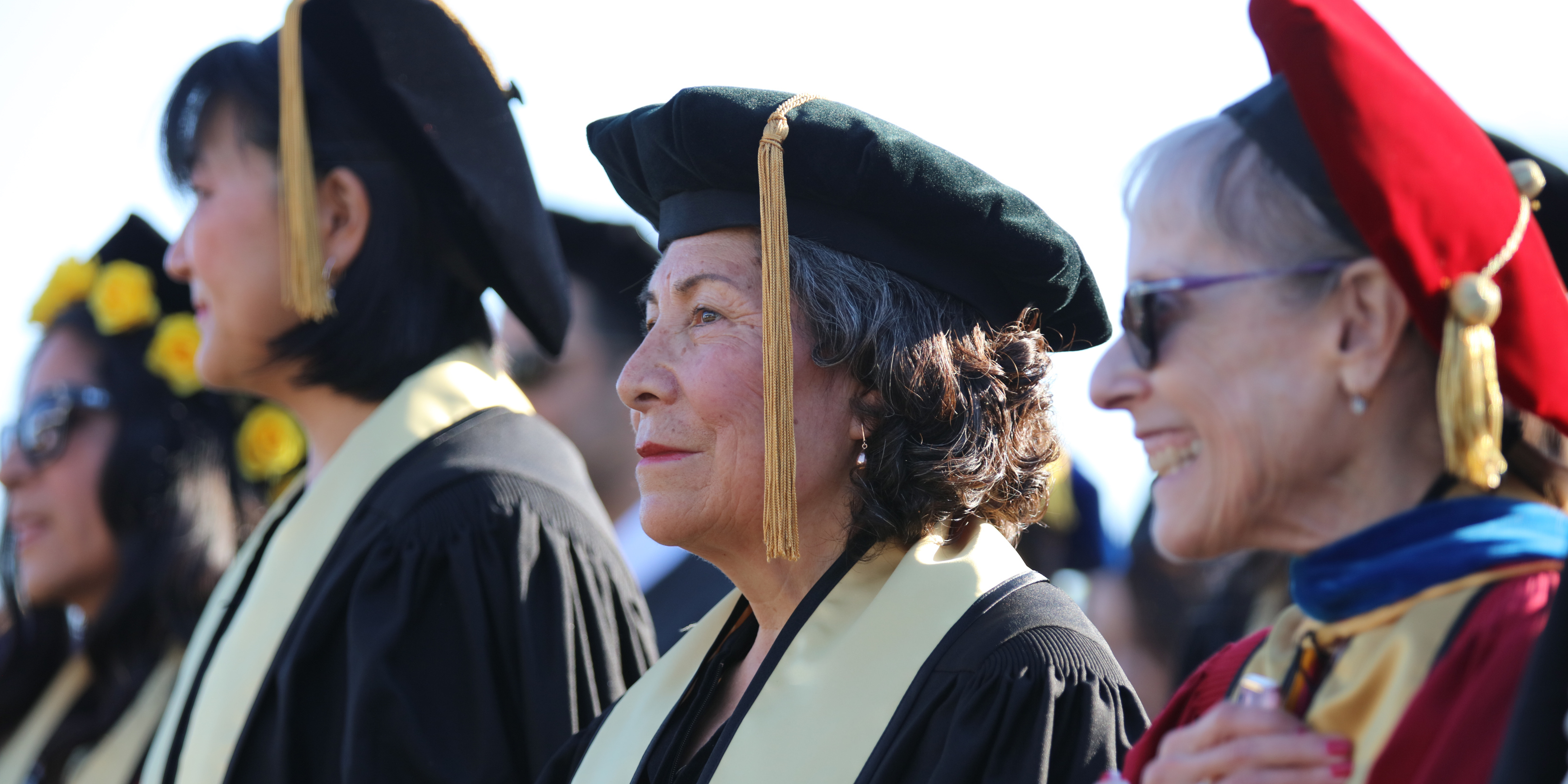 Doctoral student between faculty at commencement, all wearing robes, hoods, and tams