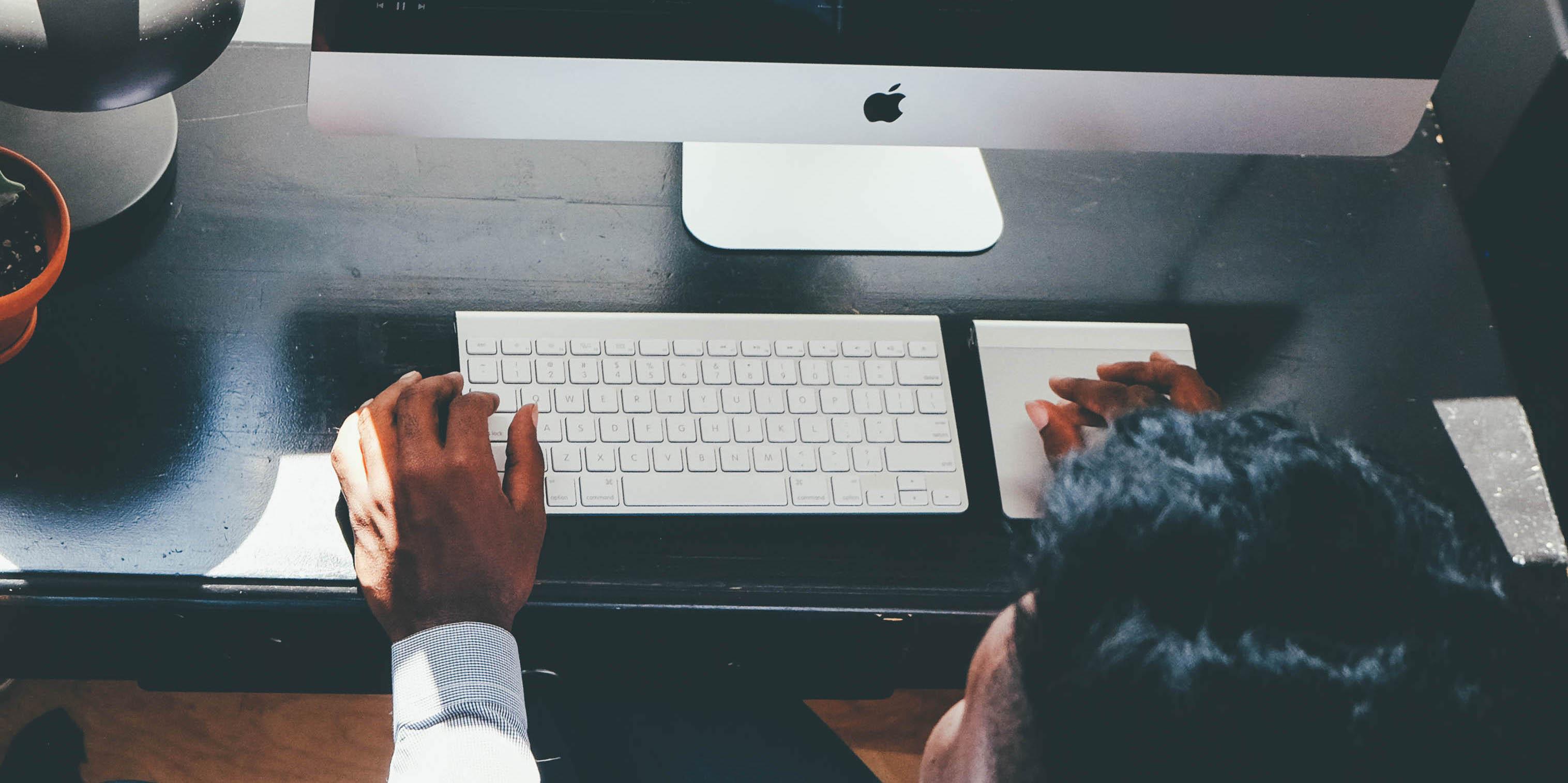 Person sitting at a desk, looking at computer monitor