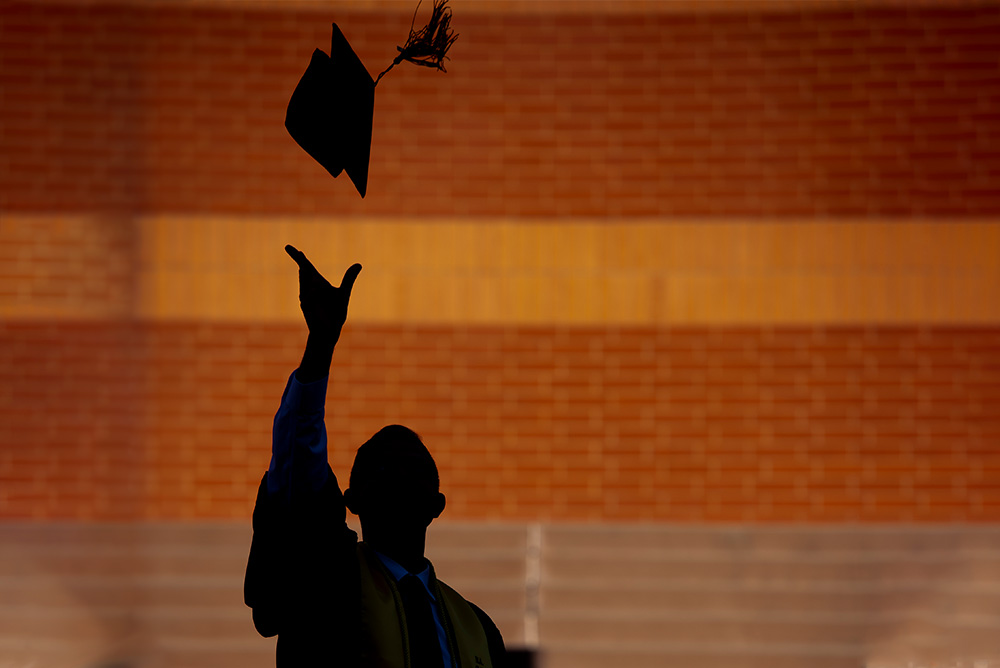 Shadow of grad against building wall throwing a cap