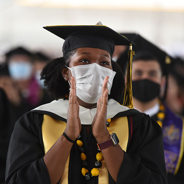 Graduate in mask clapping at Commencement