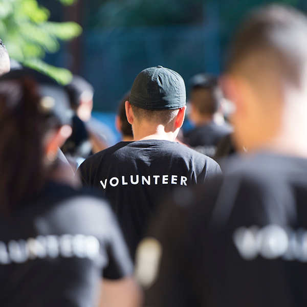 crowd of people with volunteer on back of shirts