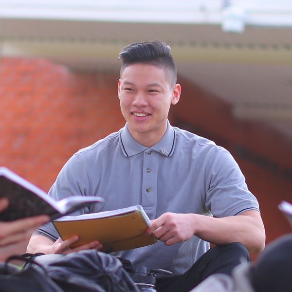 Student holding a notebook outdoors