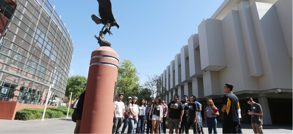 Students visting eagle sculpture during campus tour.