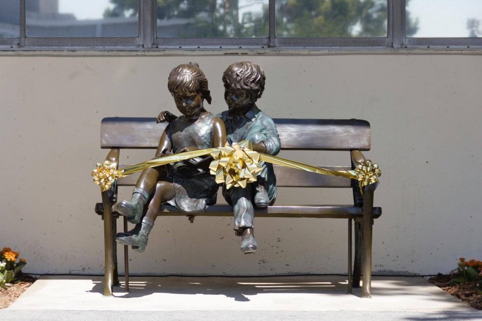 A bench with metal statues of children sitting. The bench is wrapped in gold ribbon and bows.