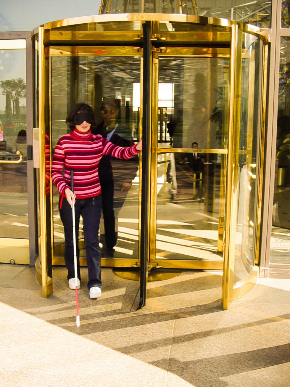 2002 Cal State LA O&M student (and now part-time faculty) Robyn Herrera practices navigating revolving doors with the long cane.