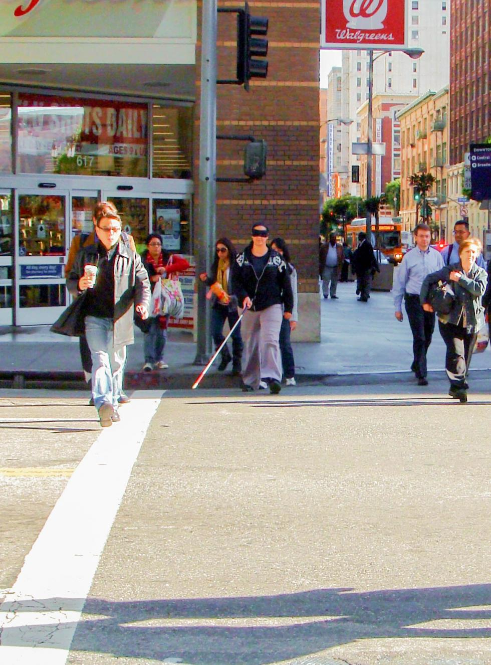 2011 Cal State LA students practice simulated travel in downtown LA – pictured Tamar Tashjian crossing the street amidst pedestrians, using her long cane