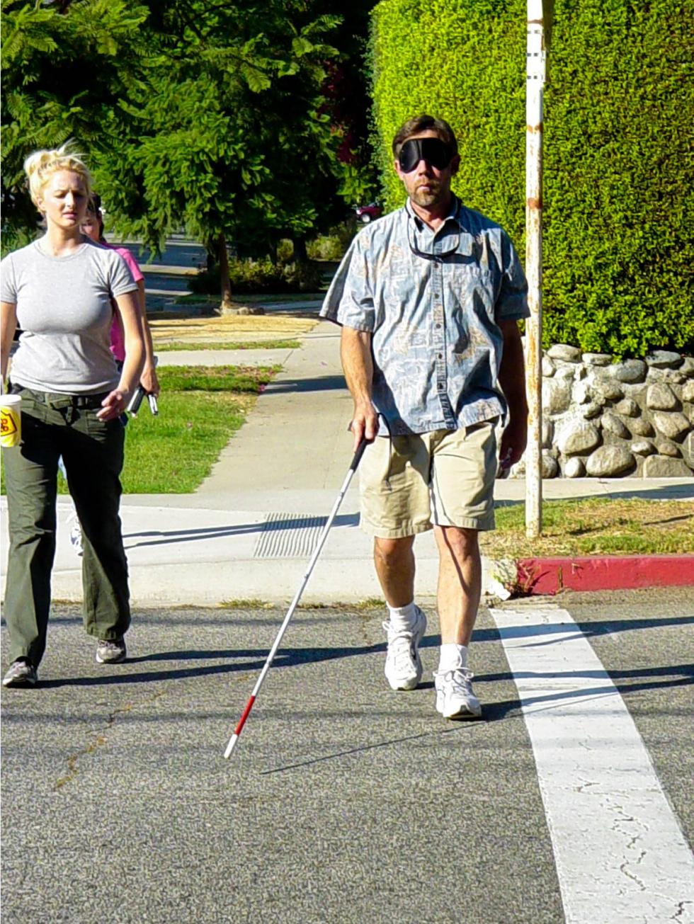 2004 Cal State LA O&M graduates practice simulated travel and teaching in a residential environment - pictured Keith Tomlinson using two-point touch can technique as he crosses the street and Layna Marshall monitoring his travel.