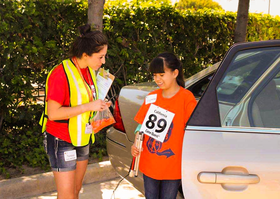 Participant exiting a vehicle and getting encouragement from volunteer Teresa