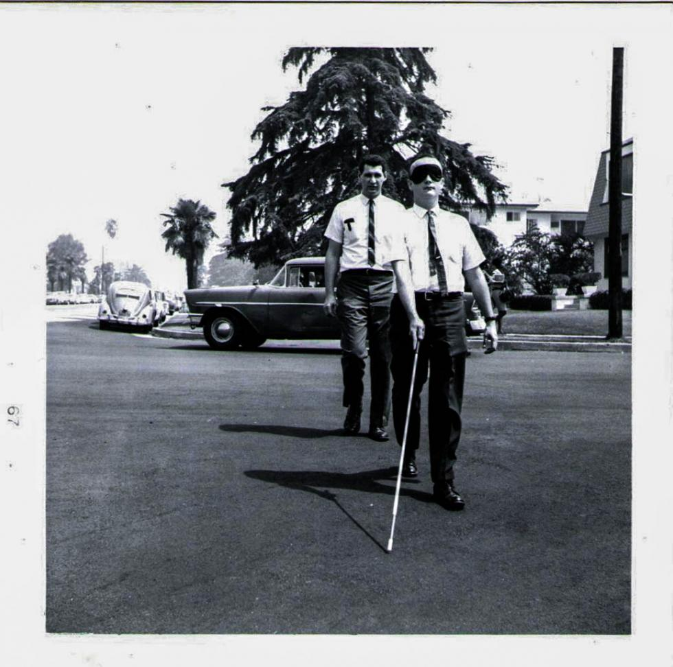 Cal State LA simulated travel along a sidewalk – 1967, Robert Eisenberg, O&M Program Faculty, monitoring