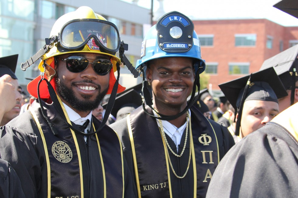 Fire Protection graduates wearing gowns and helmets at Commencement