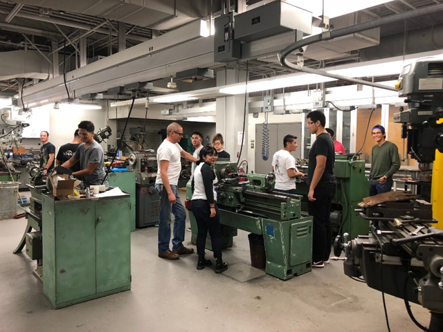 Students working with machines in the Kenneth R. Thomas Machine Tool Lab