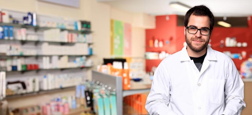 Pharmacy techician in a pharmacy with medications shelved behind him