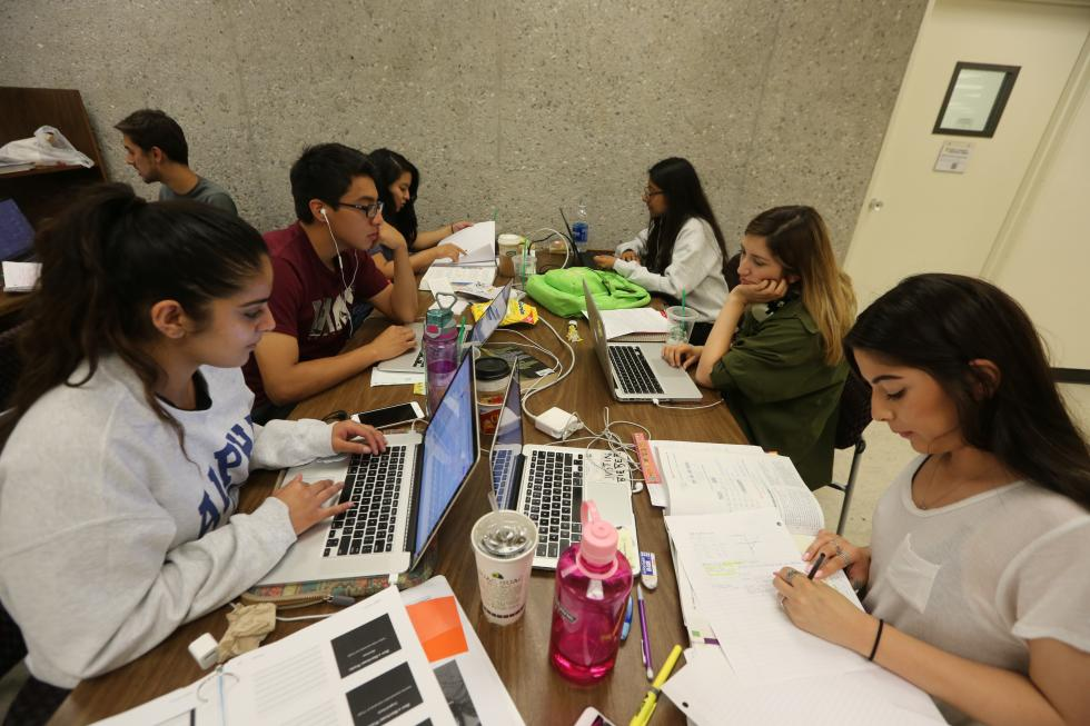 A group of students studying around a table with books and computers