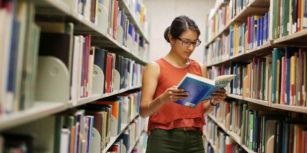 Student reading book, standing between two shelves of books in library