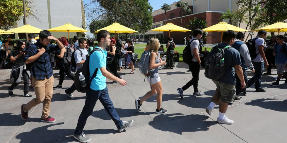 Students walk past tables with umbrellas on Main Walkway