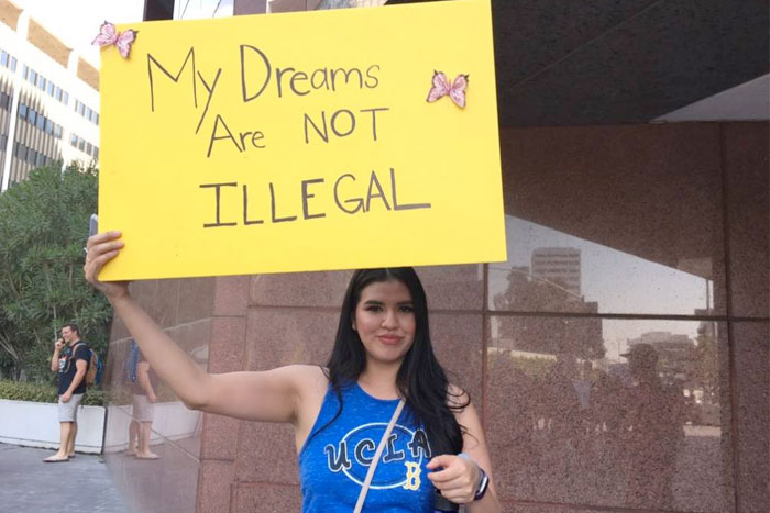 "Protestor holds sign ""My dreams are not illegal"""