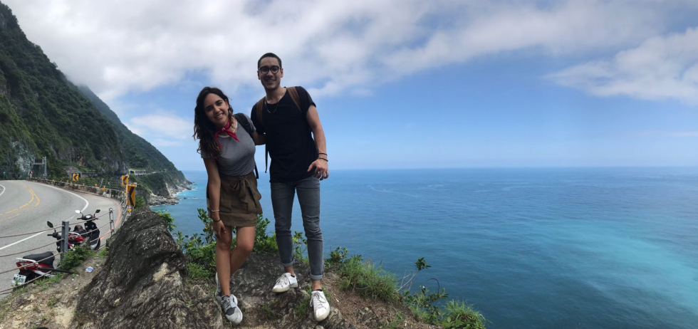 Cal State LA Student Jose Andres (right) and friend in Taiwan. They are standing on a cliff overlooking the ocean with mountains in the background.
