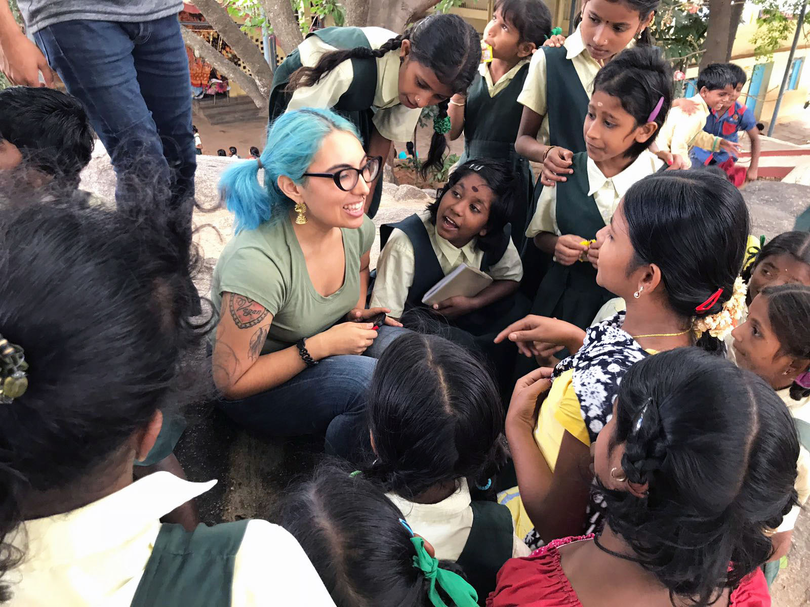 Smiling Cal State LA student sitting on the ground surrounded by listening young school students in India.