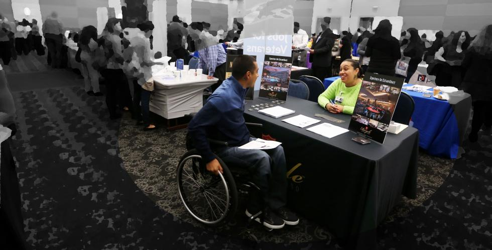 Student in a wheelchair talking to a recruiter at the Veteran's and Persons with Disabilitie's Career Fair.