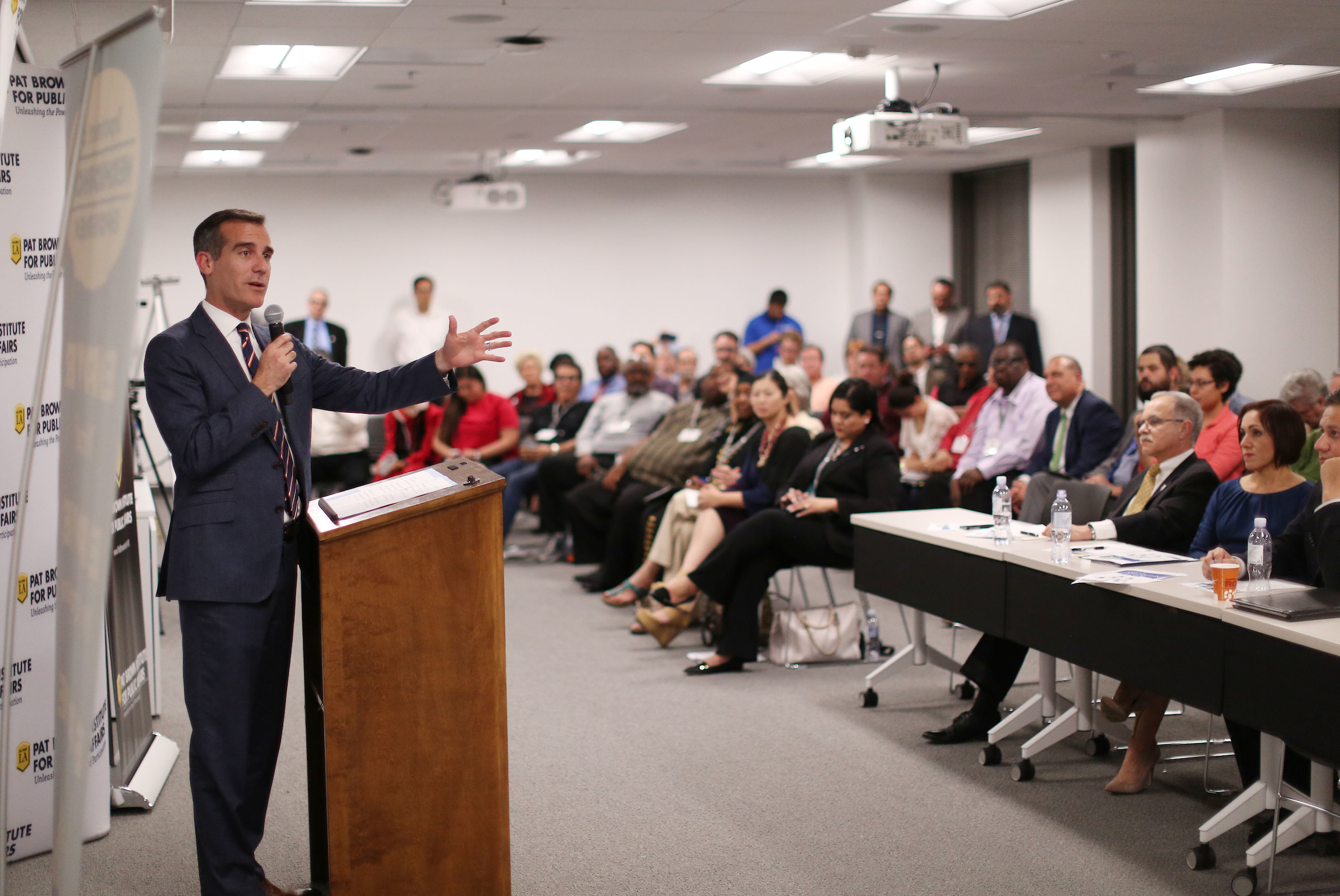 Mayor Eric Garcetti speaks with a microphone to a room full of participants of Civic University, a program organized by the Pat Brown Institute for Public Affairs at Cal State LA.
