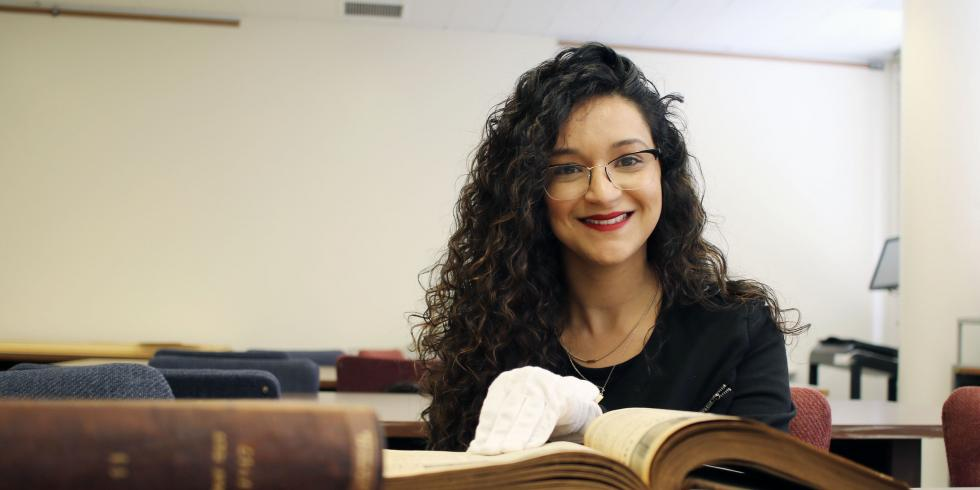 Amalia Castaneda wears white gloves, with her hand in an old book, and smiles at the camera