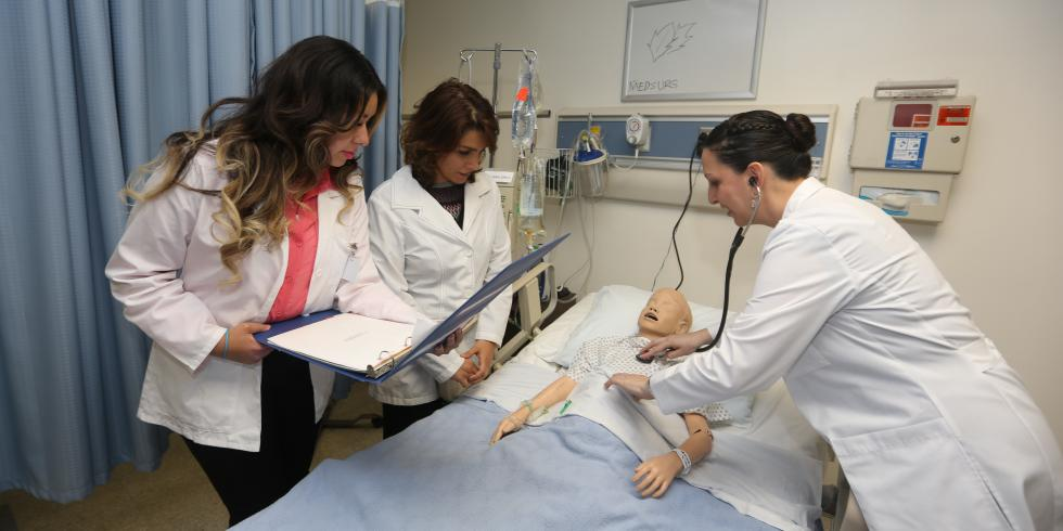 Three nursing students in white coats assist a CPR manikin
