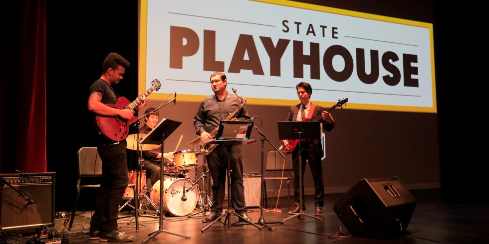 Three students play instruments on stage at State Playhouse