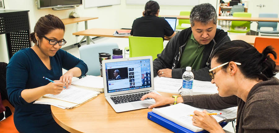 Three graduate students sit around a table studying, looking at sheet music and a video on one student's computer