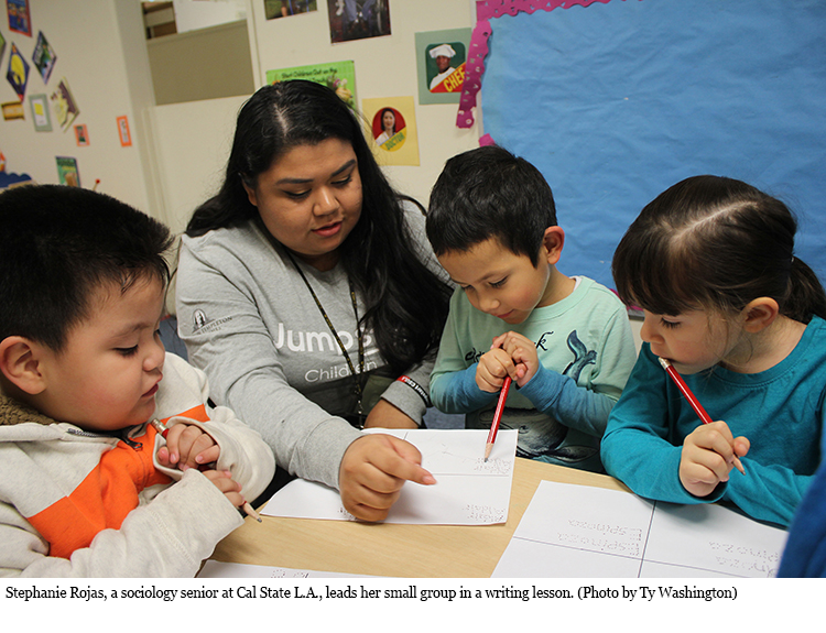 Stephanie Rojas, a sociology senior at Cal State L.A., leads her small group in a writing lesson.
