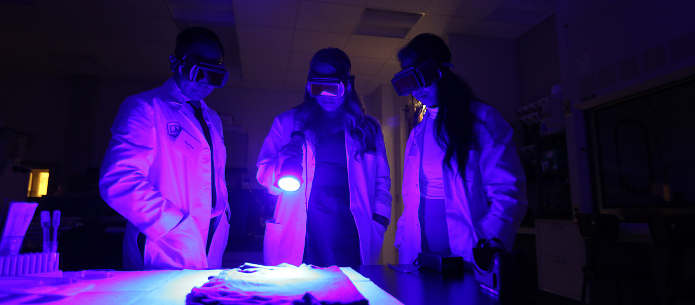 Three Criminalistics Student using a UV alternate light source to search for biological stains.