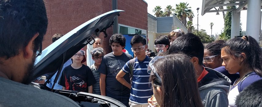 Kids observing car with open hood