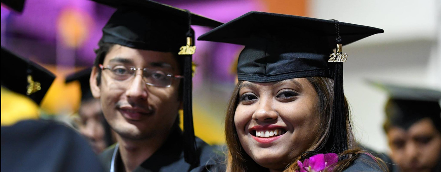 Graduating man and woman smiling for the camera