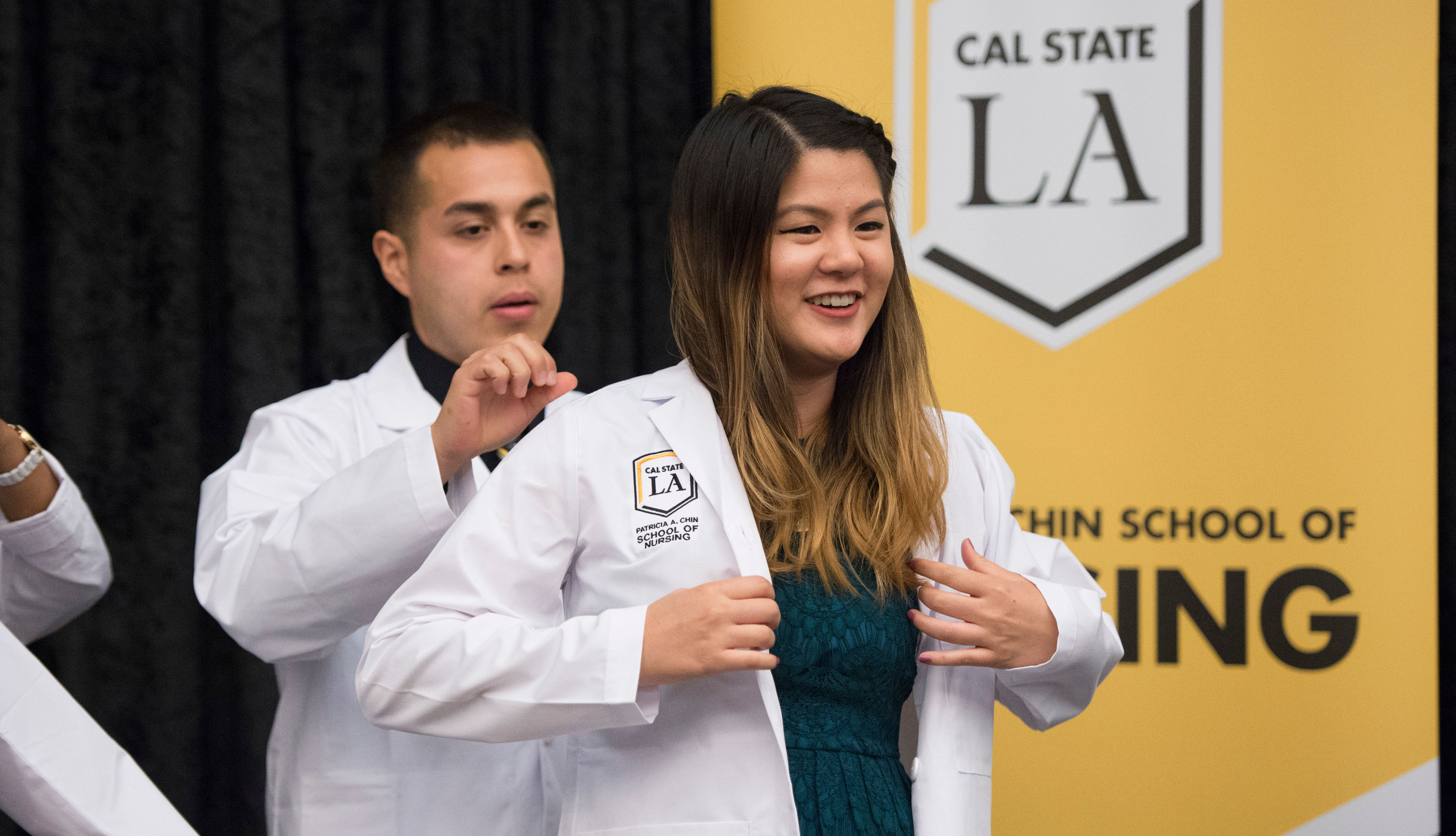 A student put on her white coat on stage.