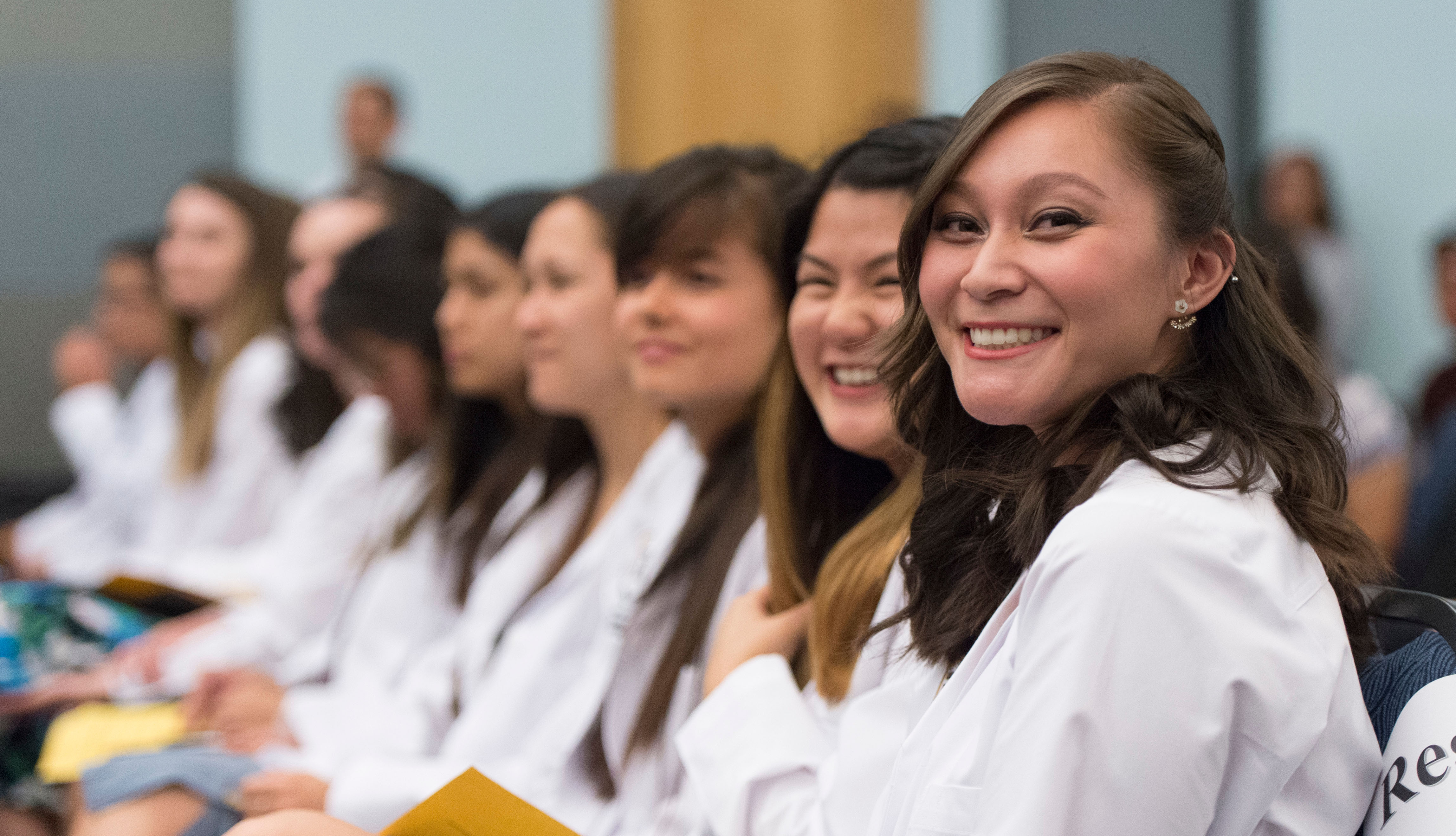 Students sit in their white coats and smile to the camera.