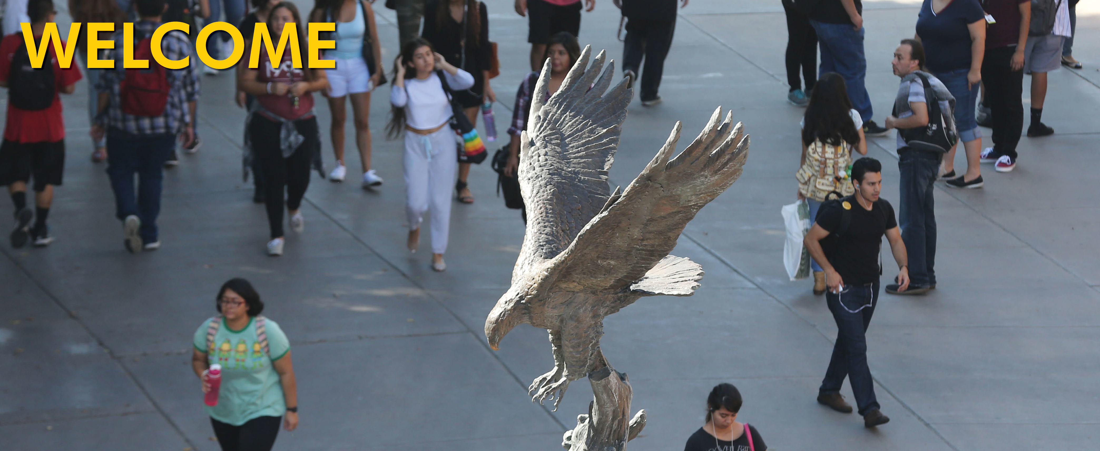 Students walking by Golden Eagle Statue