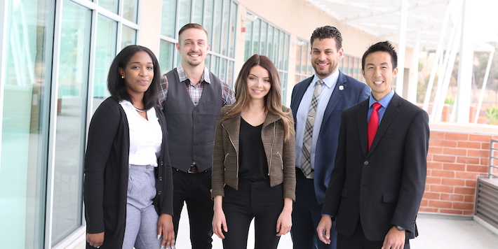 Five students in business attire stand together smiling.