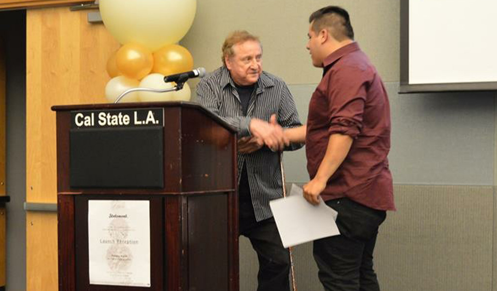 Ron Pettie, director of the Colonnade Art Gallery and Studios, presents an award to Emilio Guerra.