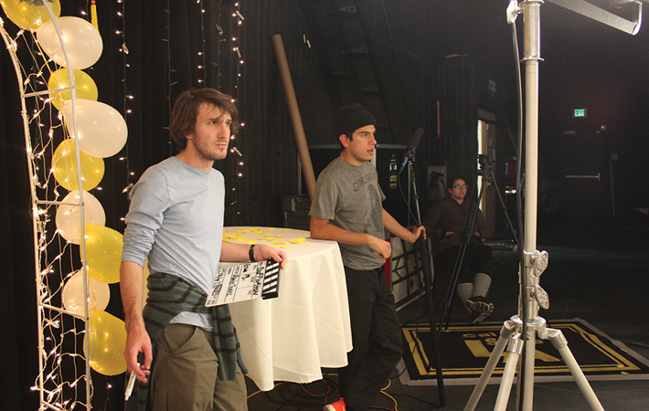 Second-year M.F.A. student Todd Leiser, left, prepares the clapboard for the next scene while filming in the soundstage. Photo courtesy Candice Clasby.