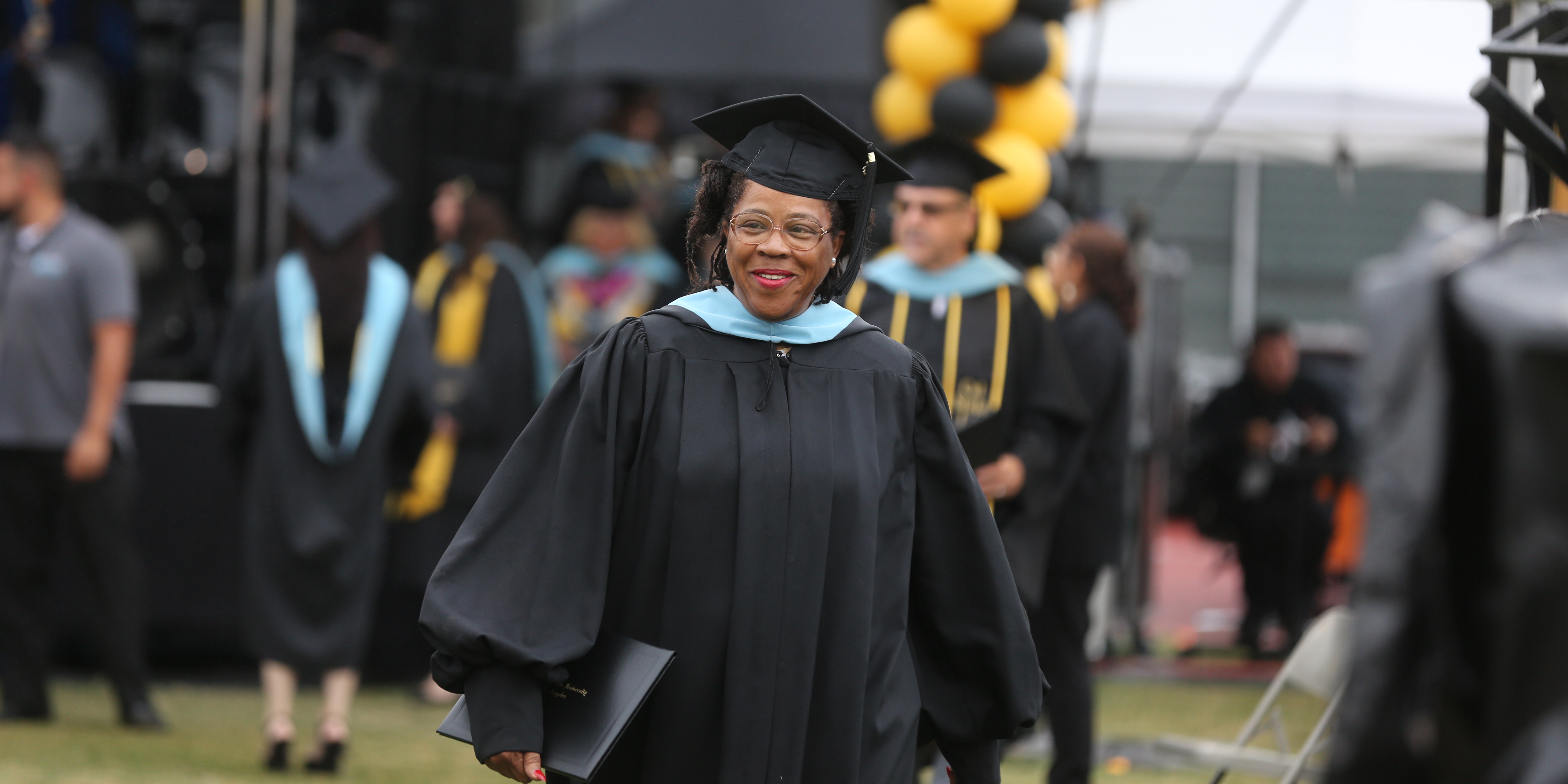 A doctoral student wears a tam, gown, and hood and carries a diploma at commemencement