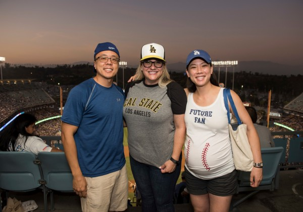 One man and two women posing with Dodger and Cal State LA baseball caps.