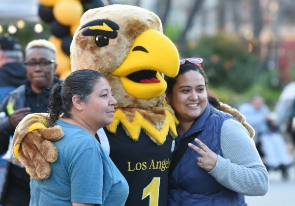 Two female alums standing with Eddie the Eagle.