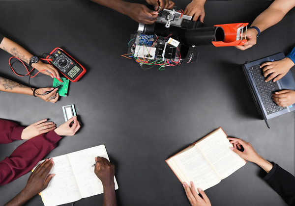 students on showing holding tools electronics
