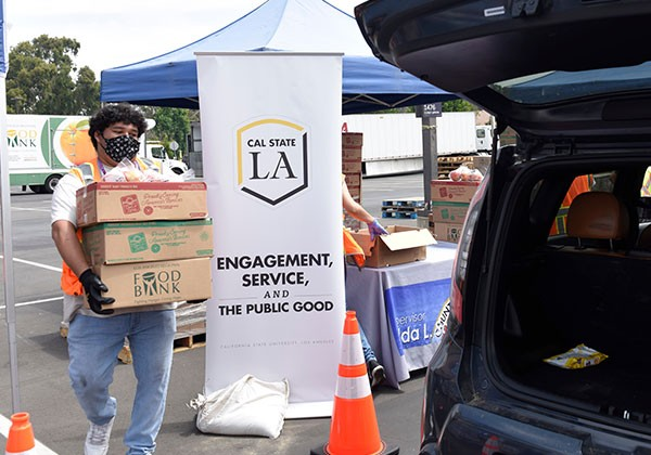 Cal State LA food drive volunteer carries boxes of food to load to the trunk of a car