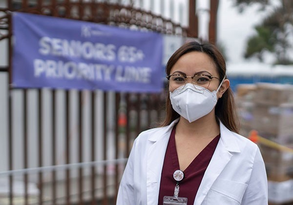 Nurse in face mask in front of banner that reads Seniors 65+ Priority Line