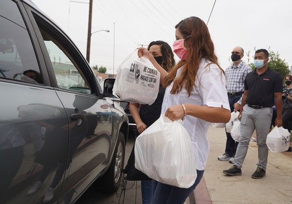 Volunteers give bags of food to car