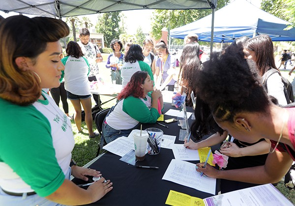 Student signing up for services eat SHAC booth