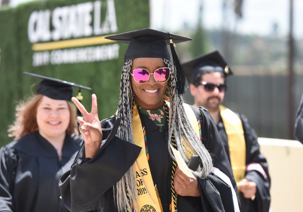 Graduating student giving a peace sign.