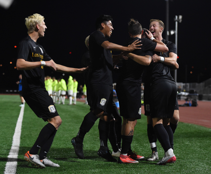 Men's soccer players in black uniforms celebrate after a goal on the field