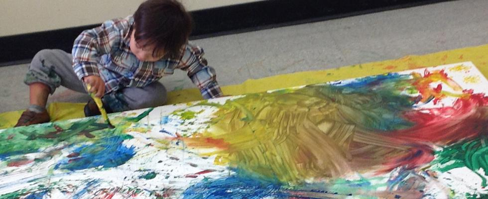 Photo of child painting on ground