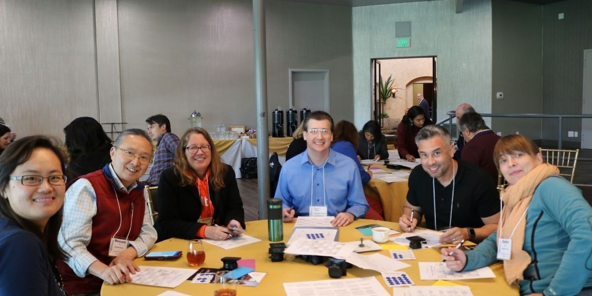 Male and female faculty members with names tags around a table smiling at camera